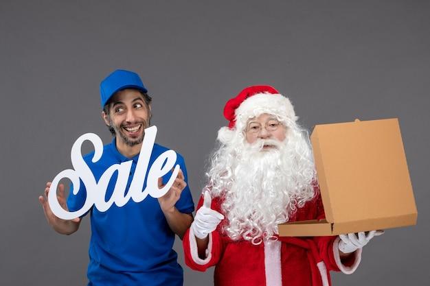 灰色の壁に販売バナーとフードボックスを保持している男性の宅配便でサンタクロースの正面図