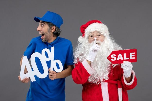 회색 벽에 판매 배너를 들고 남성 택배와 산타 클로스의 전면보기