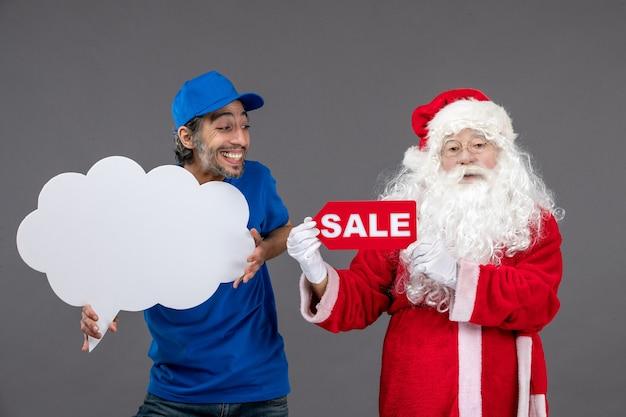 회색 벽에 판매 쓰기와 구름 기호를 들고 남성 택배와 산타 클로스의 전면보기