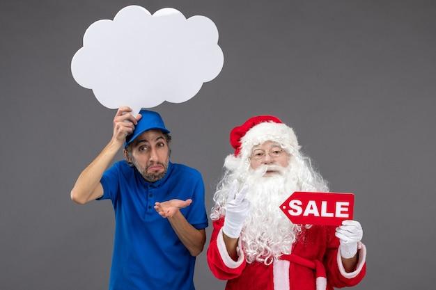 Вид спереди санта-клауса с мужчиной-курьером, держащим знак белого облака и распродажу на серой стене