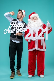파란색 벽에 새해 복 많이 받으세요 및 2021 보드를 들고 남성과 산타 클로스의 전면보기