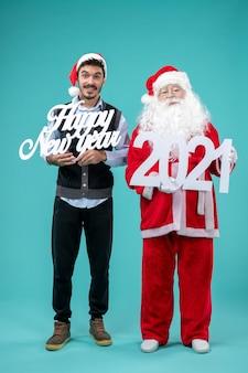 파란색 벽에 새 해 복 많이 받으세요 및 쇼핑백을 들고 남성과 산타 클로스의 전면보기