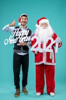 파란색 벽에 새 해 복과 2021 보드를 들고 남자와 산타 클로스의 전면보기
