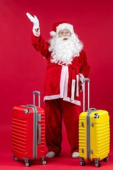 赤い壁に旅行の準備をしている2つのバッグとサンタクロースの正面図