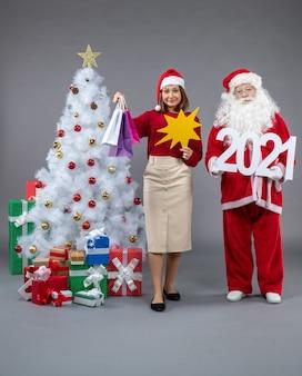 ショッピングバッグと灰色の壁に黄色の看板を持っている女性とサンタクロースの正面図