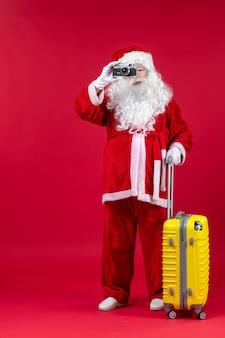 赤い壁にカメラを保持している黄色のバッグとサンタクロースの正面図