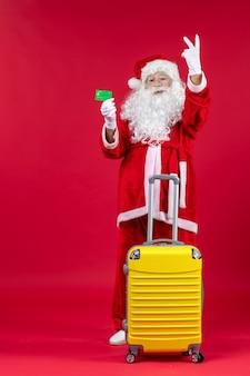 빨간 벽에 녹색 은행 카드를 들고 노란색 가방 산타 클로스의 전면보기