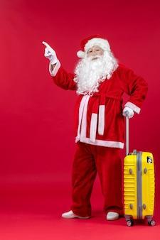 赤い壁に旅行の準備をしている黄色いバッグとサンタクロースの正面図