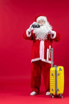 赤い壁にカメラで写真を撮る黄色いバッグとサンタクロースの正面図