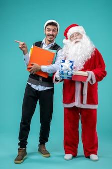 若い男性と青い壁にプレゼントとサンタクロースの正面図