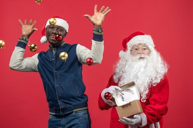 若い男と赤い壁にクリスマスツリーのおもちゃの周りのサンタクロースの正面図