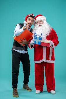 若い男と青い壁にプレゼントとサンタクロースの正面図