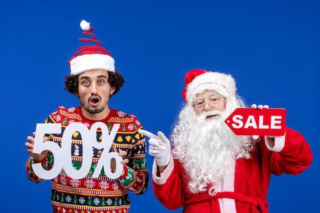 파란색 벽에 젊은 남자가 들고 판매 글과 산타 클로스의 전면보기
