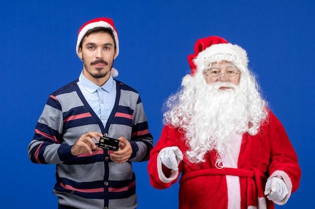 青い壁に銀行カードを保持している若い男とサンタクロースの正面図