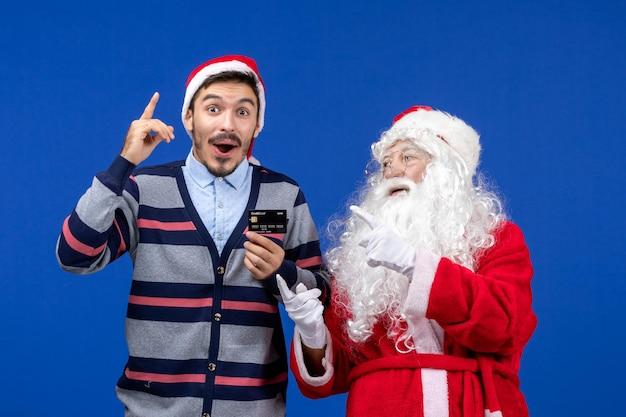 파란색 벽에 은행 카드를 들고 있는 젊은 남자와 산타 클로스의 전면 보기