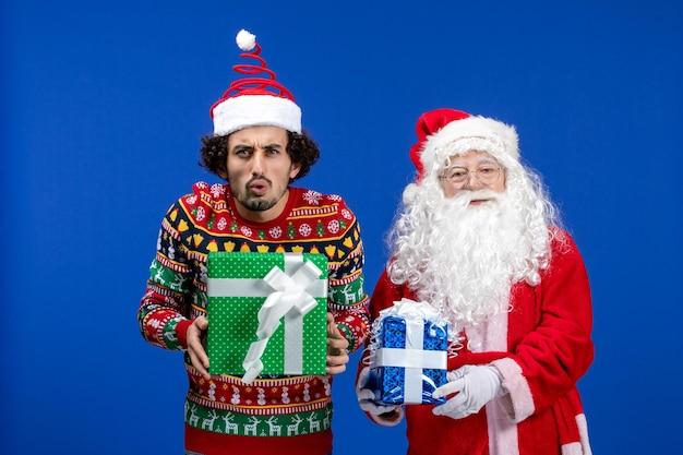 파란색 벽에 크리스마스 선물을 들고 있는 젊은 남자와 산타 클로스의 전면 보기