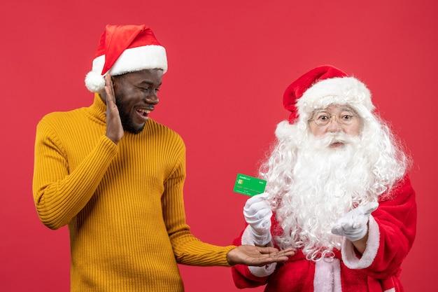 빨간 벽에 녹색 은행 카드를 들고 젊은 남자와 산타 클로스의 전면보기
