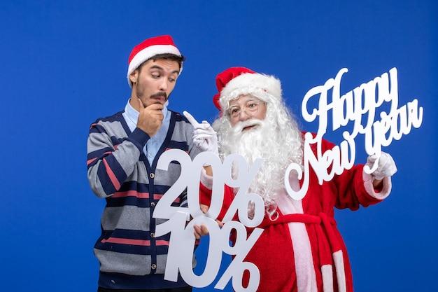 파란색 벽에 새해 복 많이 받으세요 및 숫자 글을 들고 젊은 남자와 산타 클로스의 전면 보기