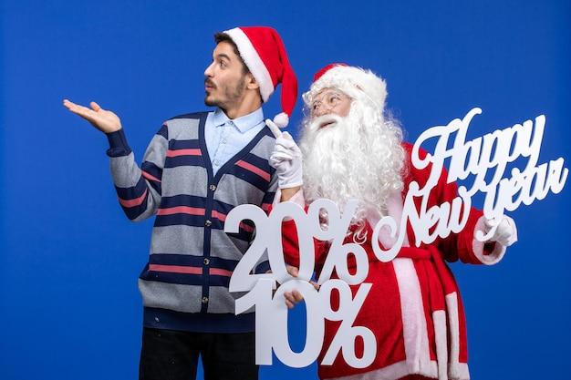 새해 복 많이 받으세요 및 파란 벽에 퍼센트 글을 들고 있는 젊은 남자와 산타 클로스의 전면 보기