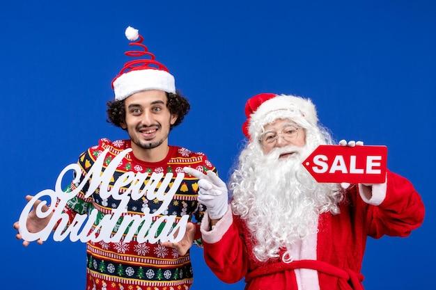 파란색 벽에 메리 크리스마스와 판매 글을 들고 있는 젊은 남자와 산타 클로스의 전면 보기