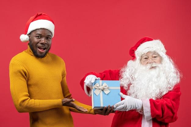 Вид спереди санта-клауса с молодым человеком, держащим подарок на красной стене