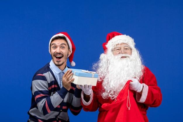 파란색 벽에 선물 가방을 들고 있는 젊은 남자와 산타 클로스의 전면 보기