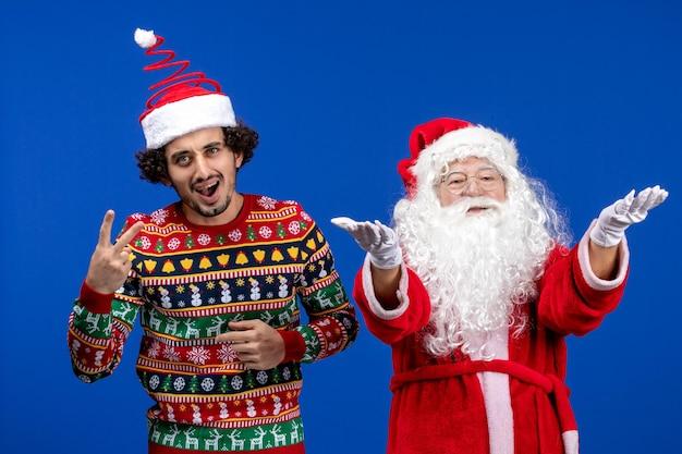 파란색 벽에 젊은 남자와 산타 클로스의 전면 보기
