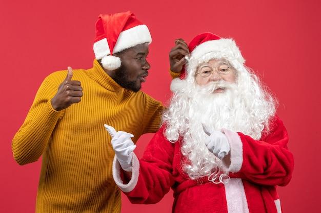 빨간 벽에 젊은 남자와 산타 클로스의 전면보기
