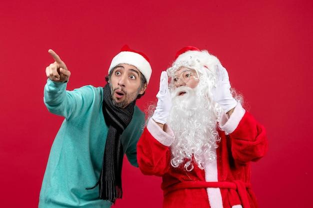 빨간 벽에 포즈를 취하는 젊은 남자와 산타 클로스의 전면 보기