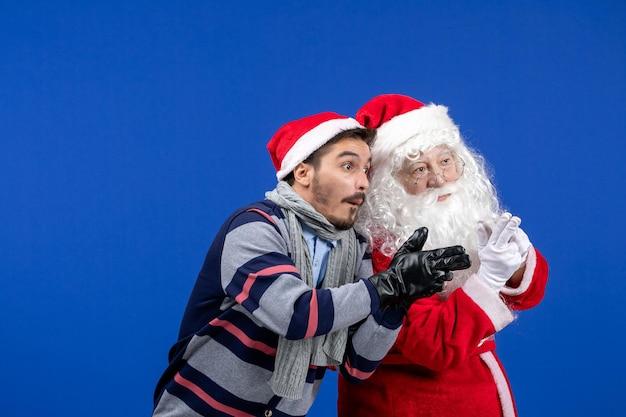 파란색 벽에 포즈를 취하는 젊은 남자와 산타 클로스의 전면 보기
