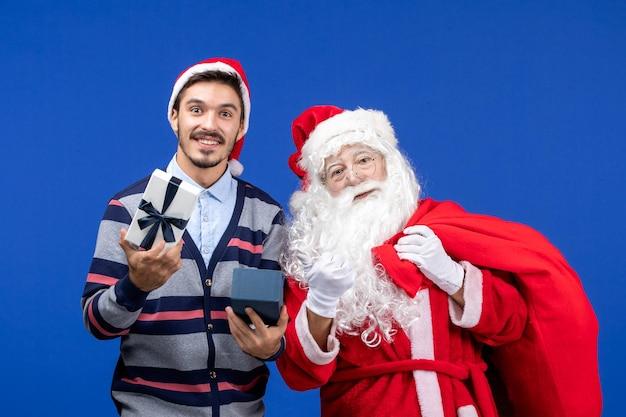 青い壁にプレゼントを開く若い男とサンタクロースの正面図