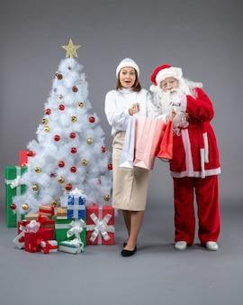 クリスマスツリーの周りと灰色の壁にプレゼント若い女性とサンタクロースの正面図