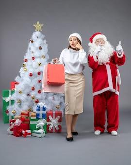 회색 벽에 크리스마스 트리와 선물 주위에 젊은 여자와 산타 클로스의 전면보기