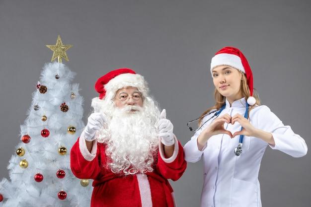 灰色の壁に若い女性医師とサンタクロースの正面図