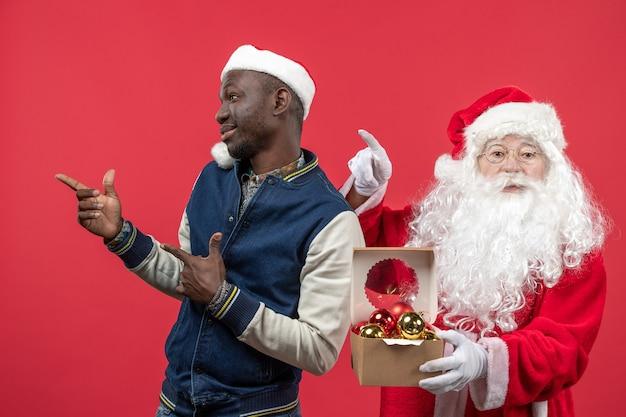 赤い壁にクリスマスツリーのおもちゃを保持している若い若い男とサンタクロースの正面図