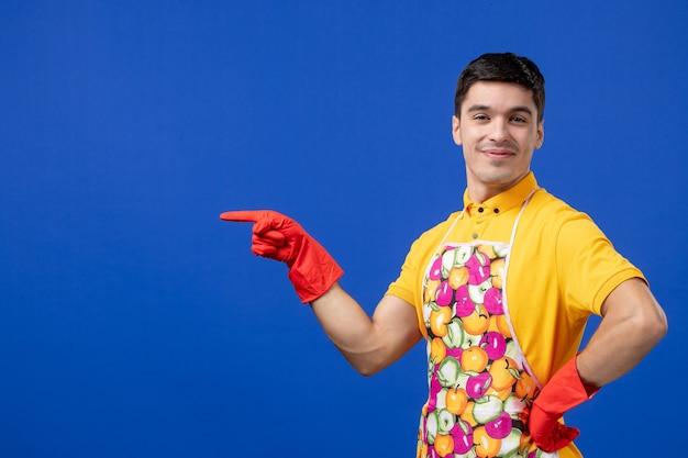 파란색 벽에 서 있는 허리에 손을 얹고 앞치마를 입은 만족한 남성 가사도우미의 전면 모습