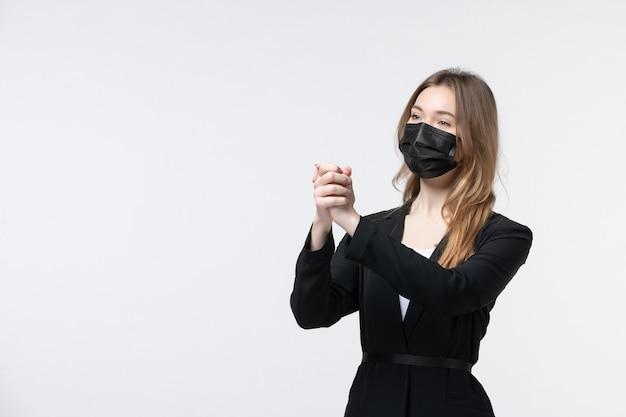 サージカルマスクを着用し、白で感謝のジェスチャーをしているスーツで満足している若い女性の正面図