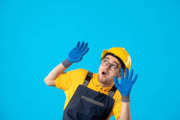 Вид спереди испуганного мужчины-строителя в униформе и перчатках на синем
