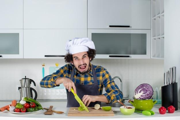 新鮮な野菜とキッチンツールで調理し、白いキッチンでピーマンを刻んで怖がっている男性シェフの正面図