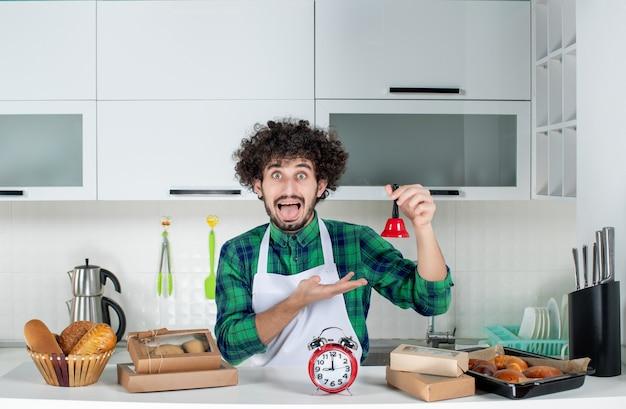 テーブルの後ろに立っている怖い若い男の正面図さまざまなペストリーと白いキッチンで赤いリングベルを示しています
