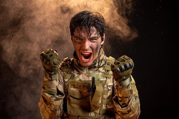 Вид спереди кричащего молодого солдата в униформе темной стены