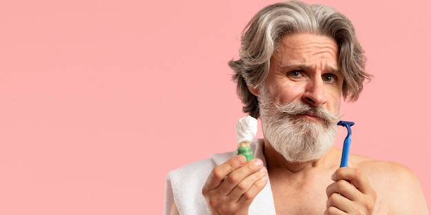 Вид спереди старшего бородатого мужчины с лезвием для бритья и пеной