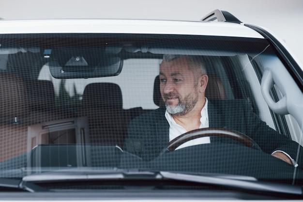 新しい機能をテストする彼の新しい現代の車の上級ビジネスマンの正面図