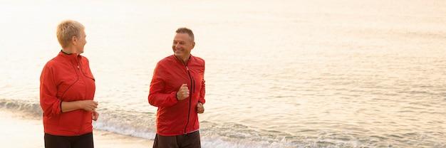 コピースペースと一緒にビーチでジョギングする年配のカップルの正面図