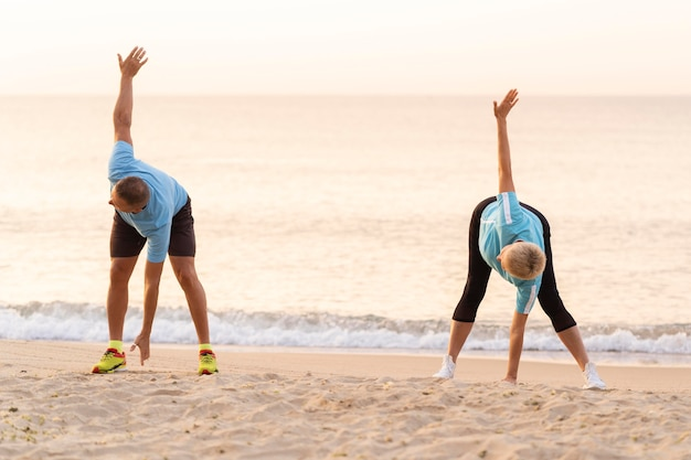 一緒にビーチでストレッチシニアカップルの正面図