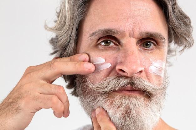 保湿剤を適用するシニア男性の正面図