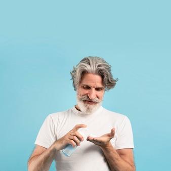 コピースペースで洗剤を使用している年配の男性人の正面図