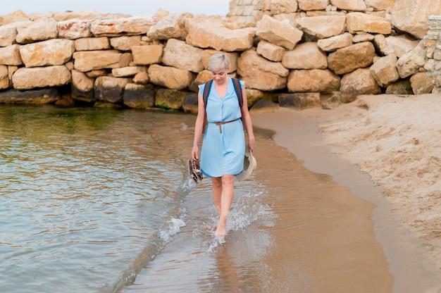 海岸沿いのシニア観光客女性の正面図