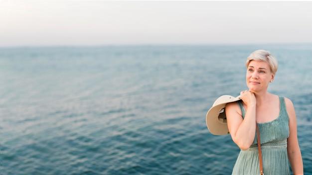 海の横にポーズシニア観光客女性の正面図