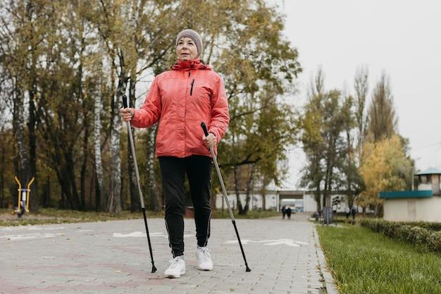 Вид спереди пожилой женщины на открытом воздухе с треккинговыми палками